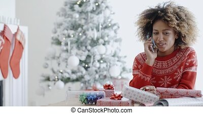 Young African woman wrapping gifts at Christmas sitting at a...
