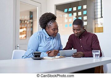 Young African work colleagues using a tablet in an office