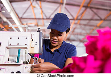 young african worker sewing in clthing factory
