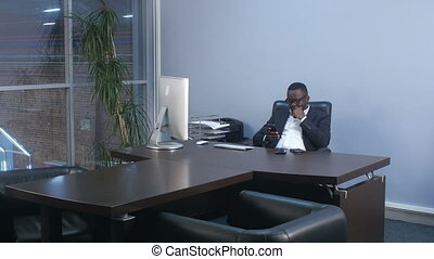 Young afro american businessman browsing with smartphone, sitting in office