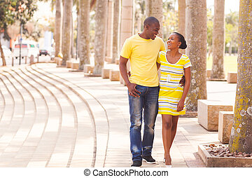 young afro american couple walking on urban street -...