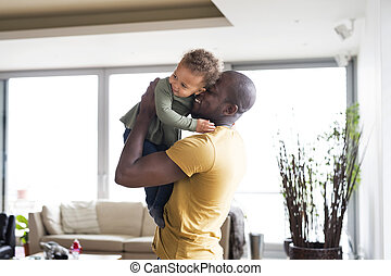 Young afro-american father with his little daughter at home....