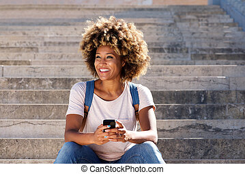 Young afro american female sitting on stairs with mobile phone and looking away
