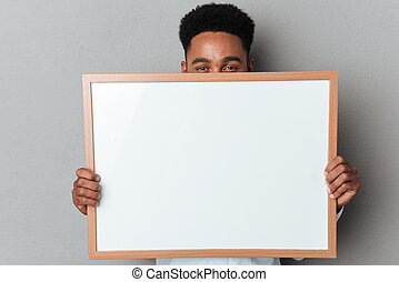 Young afro american man hiding behind blank board