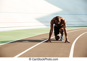Young afro american sports man in starting position ready to start on sports track at the stadium