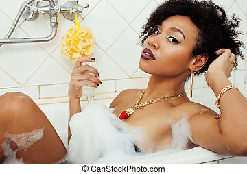 young afro-american teen girl laying in bath with foam, ...