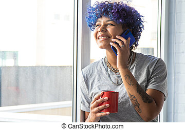 young afro american woman with mobile phone and cup of coffee at the window
