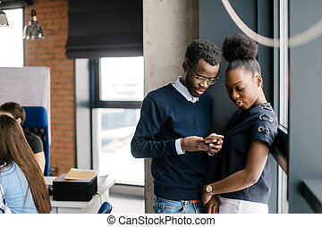 closeup portrait of young Afro couple in casual outfit using mobile phone together
