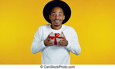 Young afro man holding gift box with bow, he wonders what is inside. Yellow wall background. African hipster guy in hat smiling, he is happy to get present