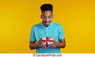 Young afro man holding gift box with bow, he wonders what is inside. Yellow wall background. African guy smiling, he is happy to get present