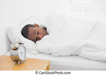 Afro man sleeping in bed with alarm clock in foreground - ...