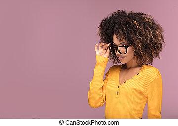 Young afro woman wearing eyeglasses, smiling.