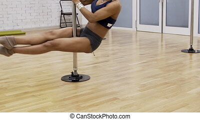 Young afroamerican sportswoman is having a pole dance work out in gym.