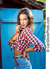 Young aggressive hipster lady in checked shirt with uncombed hair