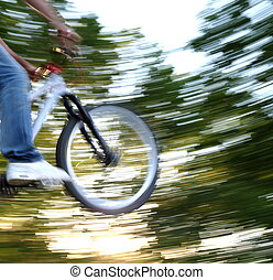 young airborne bmx biker (motion blur is used to convey movement)