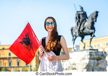Young Albanian patriot standing with flag in the center of ...