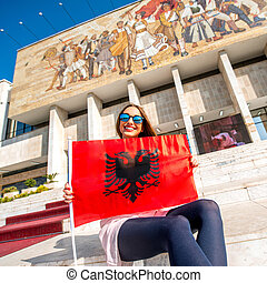 Young woman patriot with Albanian flag sitting in front of National museum in Tirana city