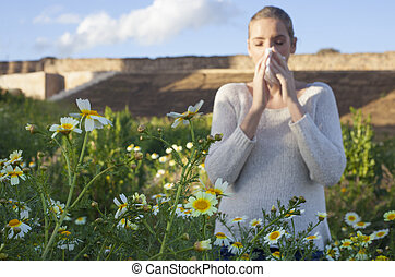 Young allergic woman sneezing in a meadow