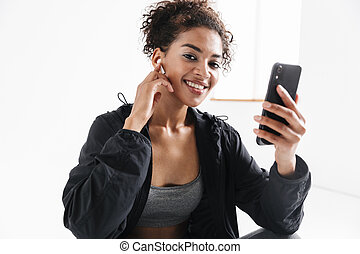 Young amazing sports fitness african woman using mobile phone listening music.
