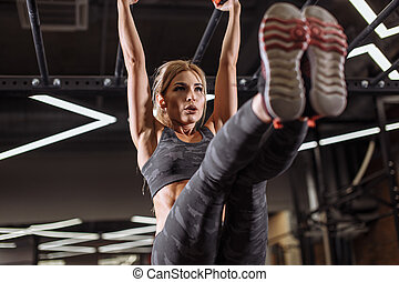 young ambitious attractive girl is training on thehigh bar