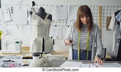 Young ambitious seamstress is taking photos of garment...