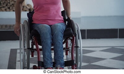 Young american disabled woman riding sitting on wheelchair...