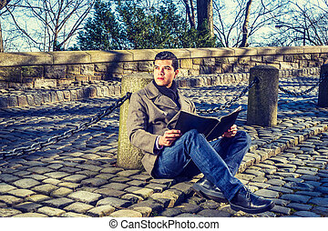 Young American Man reading magazine at park in New York in winter