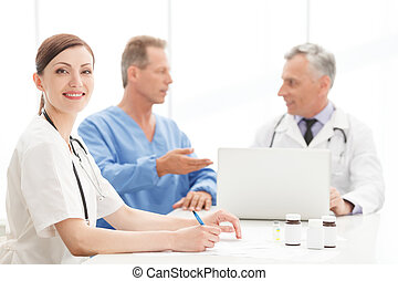 Young and ambitious. Portrait of a smart young female doctor sitting at the table in front of her colleagues and smiling