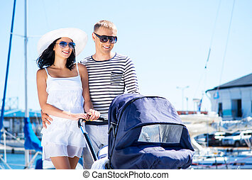 Young and attractive couple walking with a baby pram outdoor...