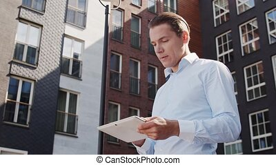 Young and attractive freelancer walking outdoor. Office ...