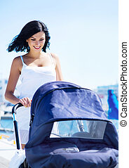 Young and attractive mother walking with a baby pram outdoor