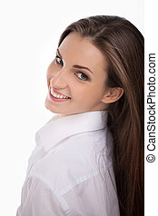 Young and beautiful. Beautiful young woman in white shirt looking over shoulder and smiling while isolated on white