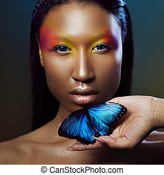 Young and beautiful black model exotic look with bright blue butterfly