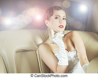 Young and beautiful celebrity woman sitting in a luxury car