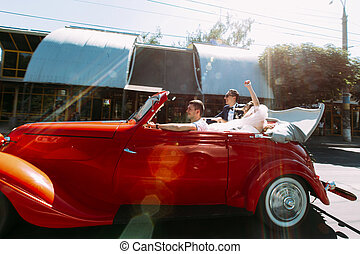 Young and beautiful couple in the red car