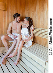 Young and beautiful couple relaxing and hugging in a sauna with towel covering up their bodies