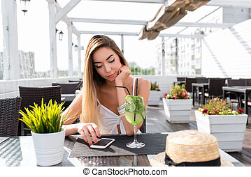 Young and beautiful girl in a cafe. On the table a glass with a cocktail green lime. A woman reads a message on phone, online on the Internet for lunch in a restaurant. In summer on the sun porch.