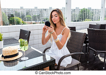 Young and beautiful girl in cafe. On table glass with cocktail green lime. A woman holds powder box her hands, applies everyday makeup. White dress and casual make-up, with long hair and tanned skin.