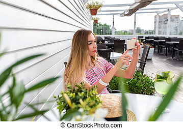 Young and beautiful girl in cafe. On table glass with cocktail green lime. A woman holds smartphone hands, listens to music in our stores. Makes video call on Internet, online photographs on phone.