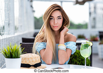 Young and beautiful girl in cafe with long hair. Portrait of woman in summer cafe. Tanned skin casual makeup. Emotionally tender smile insightful look. On table glass with green lime and straw hat.