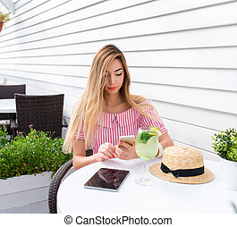 Young and beautiful girl in cafe with long hair. Reads a message on phone, online on Internet for lunch in restaurant. In summer on sun porch. On the table is a glass of green lime and a tablet.