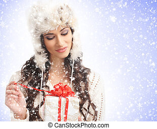 Young and beautiful girl with a present box over snowy Christmas background