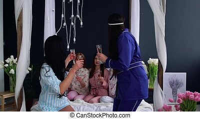 Young and beautiful girls at a bachelorette party pour...