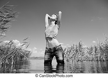 Young and beautiful savage girl in the river. Photo in noisy...