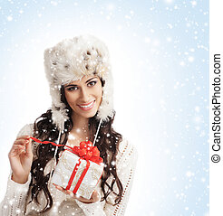 Young and beautiful woman holding a nice Christmas present over