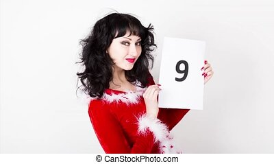 young and beautiful woman in red coat holds a sheet of paper...