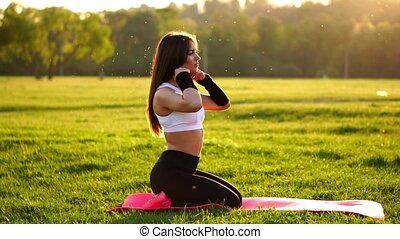 Young and beautiful woman is sitting on the mat during break in her fitness workout. Rest after exercise in the sunlight correcting the hair in slow motion. Hair in the backlight.