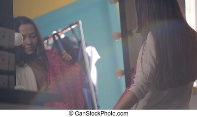 Young and beautiful woman is standing in front of mirror choosing dress.