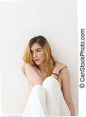 Teenage blonde girl with distant and sad look. She is leaning against a white wall. The legs are bent