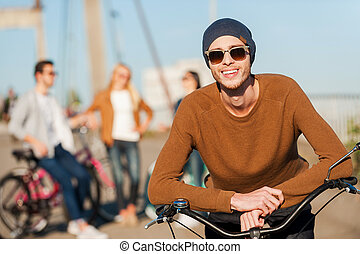 Young and carefree. Handsome young man leaning at his bicycle and looking at camera with smile while his friends talking in the background